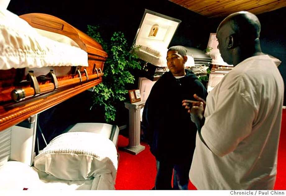 Todd Walker (right) shows a selection of caskets to Daveon Weathers when teenagers from the Berkeley Cougars football team visited the Whitted-Williams Mortuary in Oakland, Calif. on Saturday, August 5, 2006 to hear some straight talk on the dangers of life on the street. Walker, coach of the Pop Warner team, brought several teenaged boys to the funeral home to listen to stories of young men, many of them former players, whose lives ended violently.  PAUL CHINN/The Chronicle  (EDS NOTE: Todd Walker says he has obtained permission from the parents to photograph the kids)  **Todd Walker, Daveon Weathers MANDATORY CREDIT FOR PHOTOGRAPHER AND S.F. CHRONICLE/ - MAGS OUT Photo: PAUL CHINN