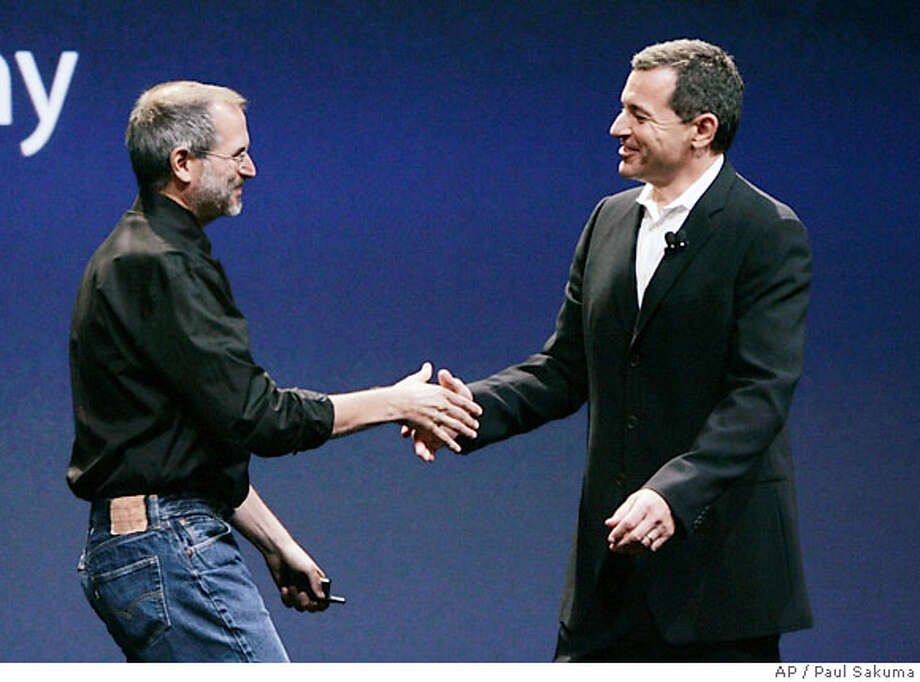 Apple Computer CEO Steve Jobs, left, shakes hands with Disney CEO Bob Iger, left, during announcement at an Apple event in San Francisco, Tuesday, Sept. 12, 2006. Apple Computer, which pioneered the online distribution of music and television shows, appears poised to jump into the movie business. (AP Photo/Paul Sakuma) Photo: PAUL SAKUMA