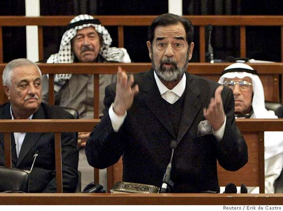 Former Iraqi President Saddam Hussein (front) testifies during his trial on genocide charges at the fortified Green Zone in Baghdad September 11, 2006. Some of Saddam's co-defendants are (middle row L-R) Sabir al-Douri and Hussein Rashid Muhammad (back row) Ali Hassan al Majid. REUTERS/Erik de Castro (IRAQ) 0 Photo: ERIK DE CASTRO