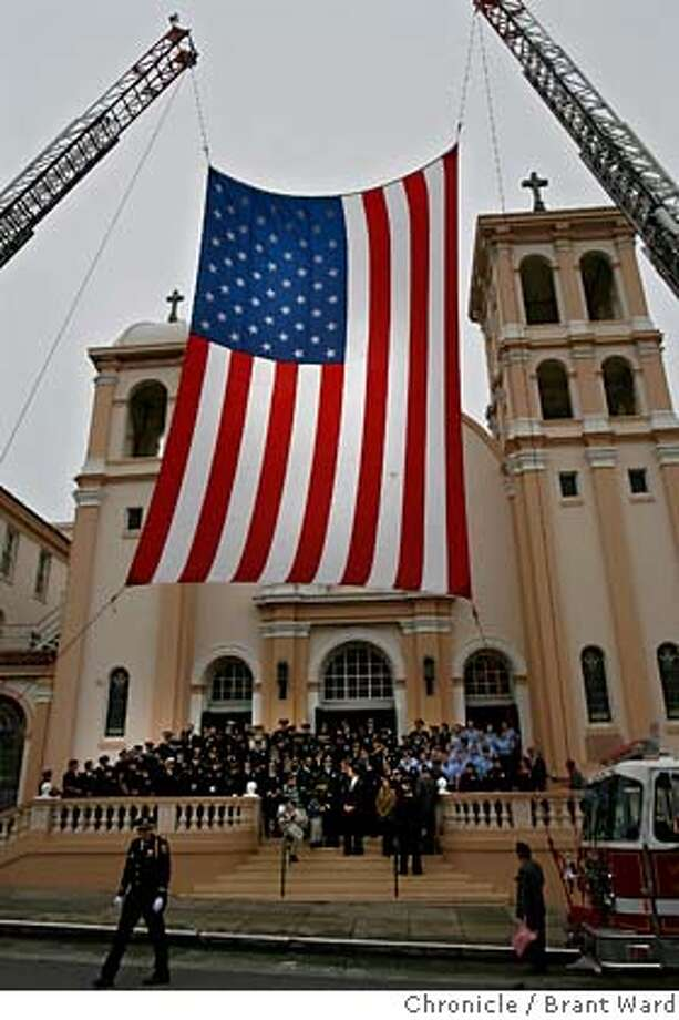 Members of the San Francisco fire and police departments posed for a picture beneath a giant American flag draped in front of St. Monica's Sunday before the mass.  St. Monica's Catholic Church at 470 24th Avenue holds its' annual 9/11 mass for fallen firefighters and police officers Sunday.  {Brant Ward/The Chronicle} 9/10/06 Photo: Brant Ward