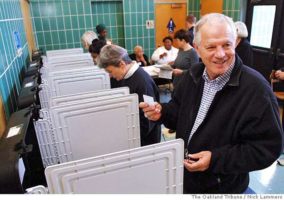 "** FILE ** Berkeley mayoral candidate Tom Bates pulls his voter card after casting his ballot Monday, Nov. 11, 2002 in Berkeley, Calif. Bates apologized Friday for an incident in which approx. 1,000 copies of a university newspaper endorsing his opponent were trashed during the recent elections. ""I deeply regret my involvement in the activity. I was tired on the last day of a difficult campaign and I made a mistake. There's no excuse for it,"" Bates said Friday, Dec. 6, 2002. (AP Photo/The Oakland Tribune, Nick Lammers) CAT MAGS OUT LOCALS PLEASE Photo: NICK LAMMERS"