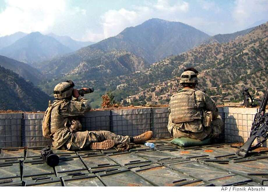 U.S. soldiers from the 3rd Battalion, 71st Cavalry Regiment of the New York-based and 10th Mountain Division control the villages of Korengal Valley by a binocular in the eastern Kunar province, as fighting continues between American troops and militants linked to al-Qaida, in Afghanistan on Sunday, Sept. 10, 2006. U.S. soldiers killed two suspected militants Sunday in a mortar barrage in the eastern Kunar province's village of Darbart after they had fired on an American-Afghan army patrol, said Command Sgt. Maj. Jimmy Carabello. (AP Photo/Fisnik Abrashi) Photo: FISNIK ABRASHI