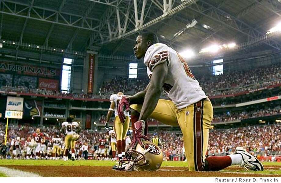 San Francisco 49ers receiver Antonio Bryant kneels in the end zone after missing a pass against the Arizona Cardinals during fourth quarter NFL action in Glendale, Arizona September 10, 2006. The Cardinals won 34-27. REUTERS/Ross D. Franklin (UNITED STATES) 0 Photo: ROSS D. FRANKLIN