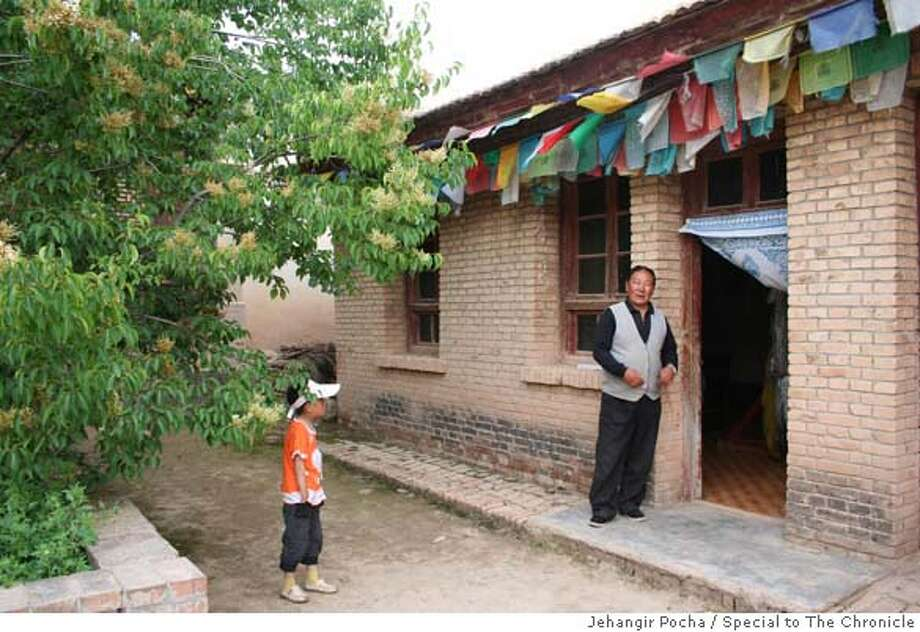 The room where the Dalai Lama was born in, with the caretaker and his daughter Gongjiashi in what is now Qinghai province. Photo by Jehangir Pocha/Special to The Chronicle  Ran on: 09-10-2006  Caretaker Gong Jiashi, with his daughter, oversees the birthplace of the Dalai Lama. Photo: Jehangir Pocha/Special To The Ch