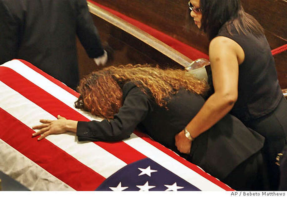 Annette Whyte collapses in grief onto the flag-covered casket of her son Marine soldier Lance Cpl. Nicholas J. Whyte, during funeral services in Brooklyn, New York, Friday June 30, 2006. Whyte, 21, of Brooklyn, died June 21 after being hit by sniper fire while on patrol in Ramadi, Iraq. (AP Photo/Bebeto Matthews)  Ran on: 07-01-2006  Annette Whyte of Brooklyn, N.Y., above, collapses in grief onto the flag-covered casket of her son, Marine Lance Cpl. Nicholas J. Whyte, during funeral services in Brooklyn on Friday. At left, Triston Whyte, 10-year-old brother to the deceased, accepts a flag during the burial ceremony at Long Island National Cemetery in Farmingdale, N.Y. Nicholas Whyte, 21, died June 21 after being hit by sniper fire while on patrol in Ramadi, Iraq.  Ran on: 07-01-2006  Annette Whyte of Brooklyn, N.Y., above, collapses in grief onto the flag-covered casket of her son, Marine Lance Cpl. Nicholas J. Whyte, during his funeral in Brooklyn on Friday. Triston Whyte, 10-year-old brother to the deceased, accepts a flag, at left, during the burial ceremony at Long Island National Cemetery in Farmingdale, N.Y. Whyte, 21, died June 21 after being hit by sniper fire while on patrol in Ramadi, Iraq. Photo: BEBETO MATTHEWS