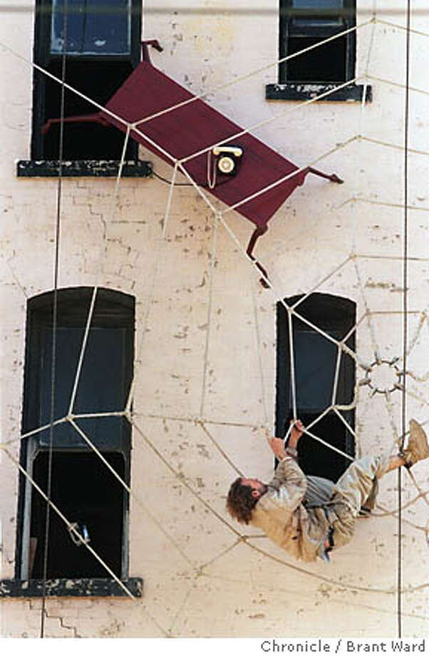 Local artist Brian Goggin works on the Defenestration Building, also known as the Hugo Hotel. The building at Sixth and Howard streets in San Francisco has been vacant more than 16 years. Chronicle file photo, 1997, by Brant Ward