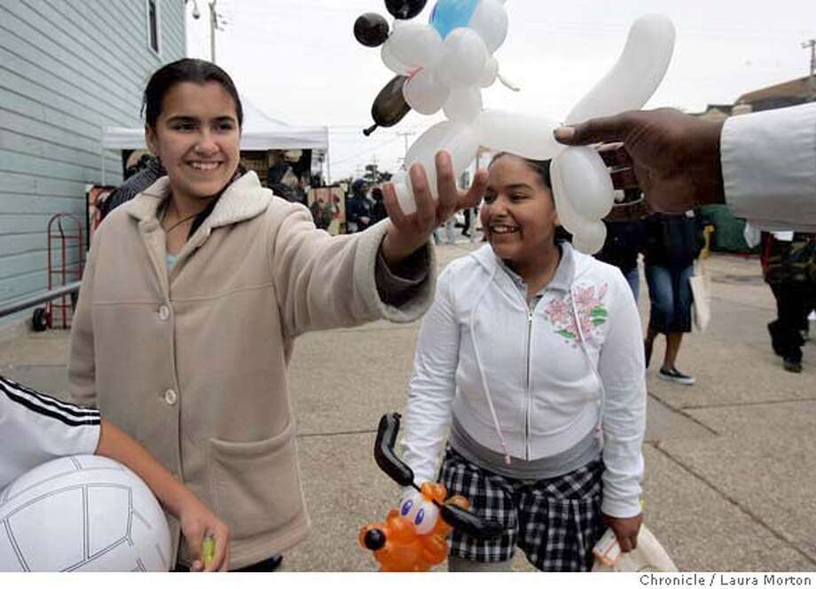 "Idalia Alfaro, age 12, and Yamilet Cruz, age 11, receive balloon animals made by Luther ""the balloon guy"" Thomas at the opening festivities for the International African Marketplace, located at the corner of 3rd and Oakdale Streets in San Francisco, CA. The marketplace is part of the Hunters Point Shipyard Redevelopment Project and even though a permanent home in the shipyard has not been sited, the market will operate every Saturday through Oct. 28, 2006. Opening festivities included performances and children's activities, along with vendors selling arts, crafts and food. MANDATORY CREDIT FOR PHOTOGRAPHER AND SAN FRANCISCO CHRONICLE/ -MAGS OUT Photo: Laura Morton"