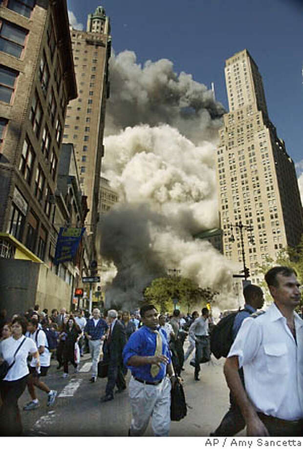Onlookers flee the area of Park Row when the World Trade Center�s south tower collapses. Associated Press file photo, 2001, by Amy Sancetta