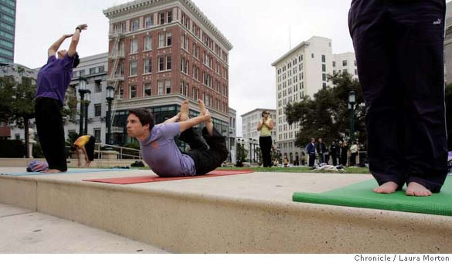 Participants in Yoga for Peace including Darby Li Po Price (left) and Evan Snow (center), practice yoga in front of the Oakland City Hall on Saturday, Sept. 9, 2006 in Oakland, CA. Participants in the event, which started in New York City as a response to 9/11, did 108 sun salutations. The Oakland event was one of several Yoga for Peace gatherings held around the world on Saturday. *** Darby Li Po Price  *** Evan Snow MANDATORY CREDIT FOR PHOTOGRAPHER AND SAN FRANCISCO CHRONICLE/ -MAGS OUT Photo: Laura Morton