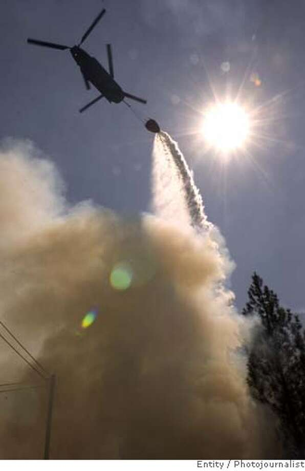A helicopter drops its load of water on a hot spot over above Oxbow Resevior, Friday, Sept. 8, 2006, near Sacramento, Calif. The Ralston Fire started Tuesday and had destroyed about 675 acres by Thursday afternoon, said Ann Westling, a fire information officer. (AP Photo/The Sacramento Bee, Randy Pench) Photo: RANDY PENCH