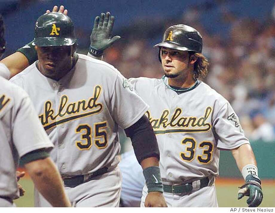 Oakland Athletics' Nick Swisher (33) heads for the dugout with Frank Thomas (35) after Swisher's grand slam off Tampa Bay Devil Rays' James Shields during the second inning of a baseball game Friday, Sept. 8, 2006, in St. Petersburg, Fla. (AP Photo/Steve Nesius) Photo: STEVE NESIUS