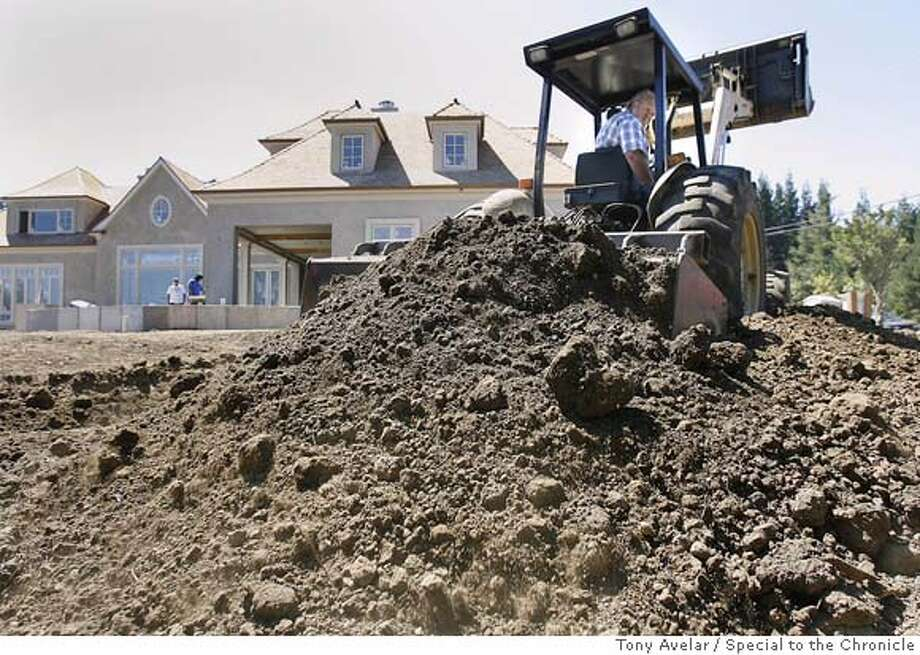 (DIRT07-1) A construction worker uses a earthmover to grade the extra dirt around a new house construction in an affluent area of Atherton. Residents are outraged by fees as high as $100,000 to cart away dirt from their property. They're especially irate because the big trend these days is to dig out basements for entertainment centers, gyms, etc. A bunch of homeowners are trying to recall the entire city council in protest. By Tony Avelar / SPECIAL TO THE CHRONICLE Photo: TONY AVELAR