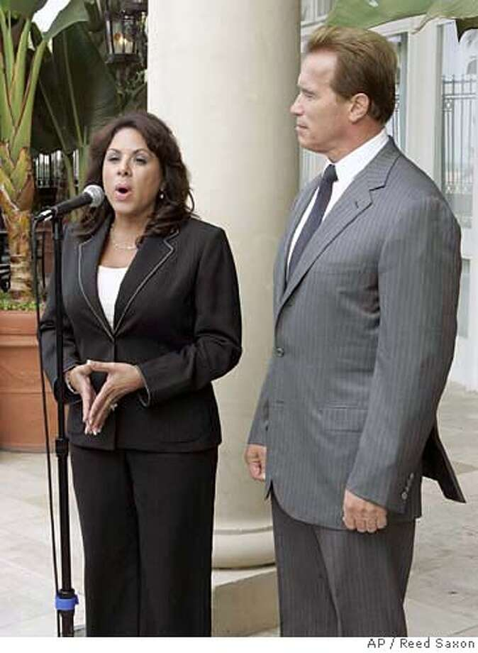 "California Gov. Arnold Schwarzenegger listens while California Assemblywoman Bonnie Garcia, R-Palm Springs, left, talks about tape-recorded comments the governor made about her at a news conference in Santa Monica, Calif., Friday, Sept. 8, 2006. Schwarzenegger apologized Friday for saying during a closed-door meeting that Cubans and Puerto Ricans are naturally feisty and temperamental because of their combination of ""black blood"" and ""Latino blood."" Garcia said she was not offended by the governor's comments. Garcia earlier told the Los Angeles Times that she often calls herself a ""hot-blooded Latina."" (AP Photo/Reed Saxon) Photo: REED SAXON"