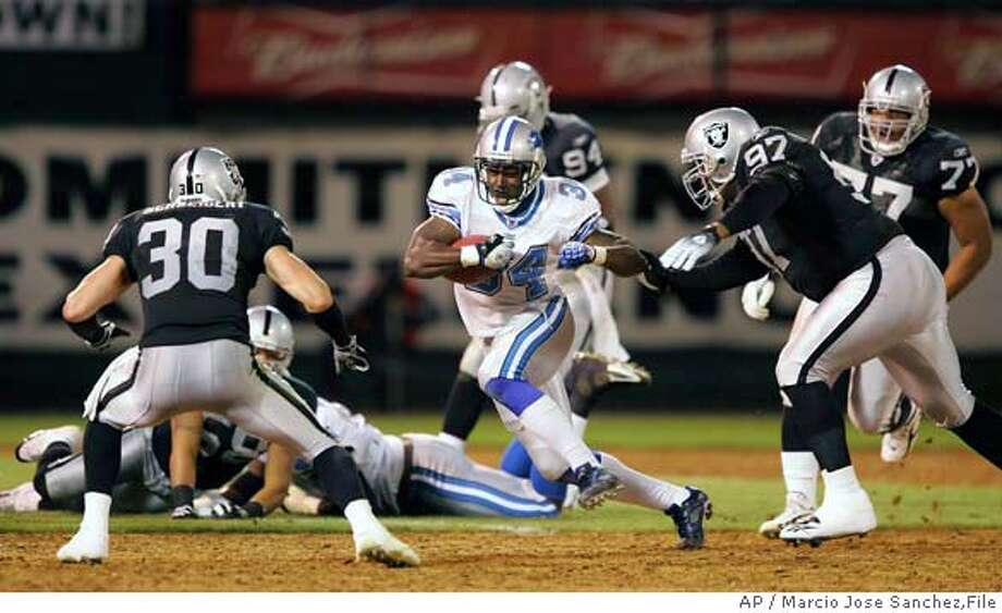 Detroit Lions running back Kevin Jones (34) runs between Oakland Raiders' Stuart Schweigert (30) and Rashad Moore (97) in the first half of their NFL pre-season football game on Friday, Aug. 25, 2006, in Oakland, Calif. (AP Photo/Marcio Jose Sanchez) Photo: MARCIO JOSE SANCHEZ