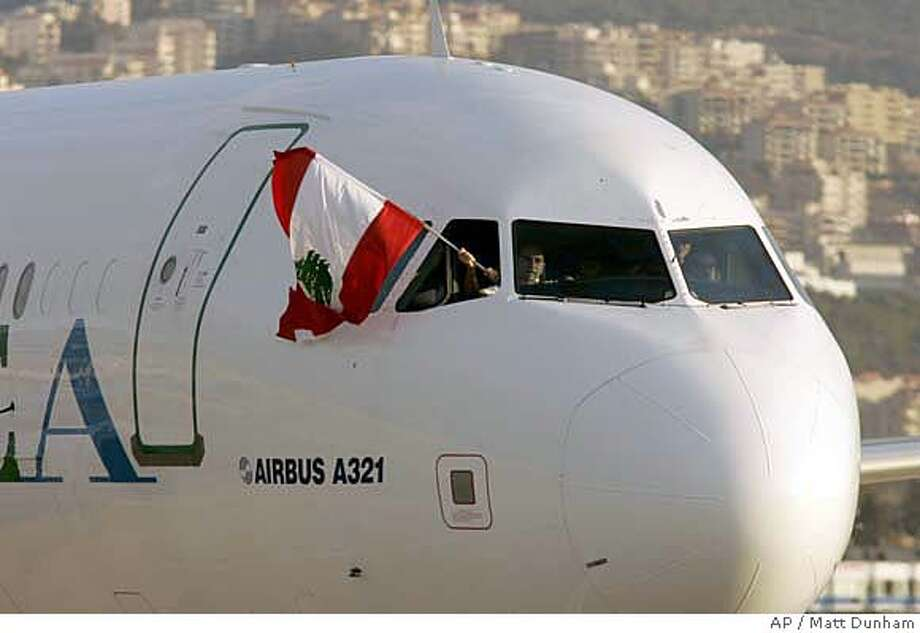 The co-pilot of a Middle East Airlines plane from Paris, the first to arrive in Lebanon after Israel's air and sea blockade was lifted at 1500 GMT on Thursday, waves a Lebanese flag from the window of the cockpit after landing at Beirut's Rafik Hariri International Airport, Thursday Sept. 7, 2006. Israel went ahead with plans to lift its air and sea blockade of Lebanon on Thursday despite objections from the army and the families of two captured Israeli soldiers, officials said. (AP Photo/Matt Dunham) Photo: MATT DUNHAM