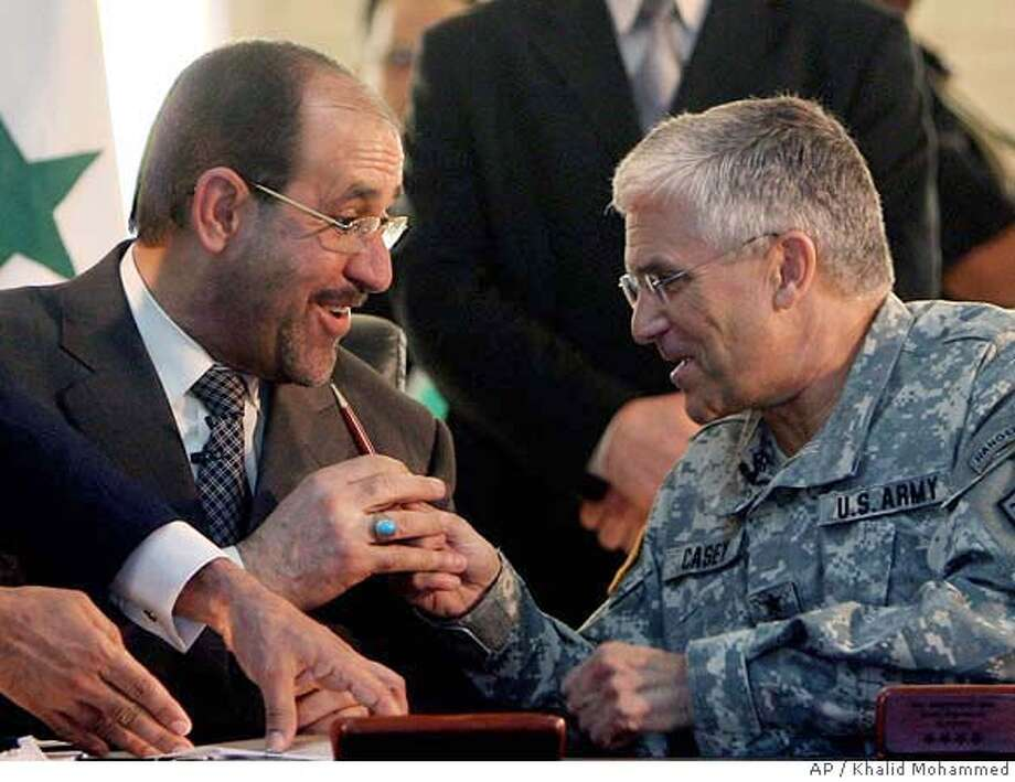 **ALTERNATE CROP OF BAG115** Iraqi Prime Minister Nouri al-Maliki , second left, takes a pen from top U.S. commander in Iraq, Gen. George Casey, after signing a document which puts the Iraqi prime minister in direct control of the country's military, at a ceremony, in Baghdad, Iraq, Thursday Sept.7, 2006. Coalition forces handed over control of Iraq's armed forces command to the government on Thursday, a move U.S. officials have hailed as a crucial milestone on the country's difficult road to independence.(AP Photo/Khalid Mohammed) **ALTERNATE CROP OF BAG115** Photo: KHALID MOHAMMED