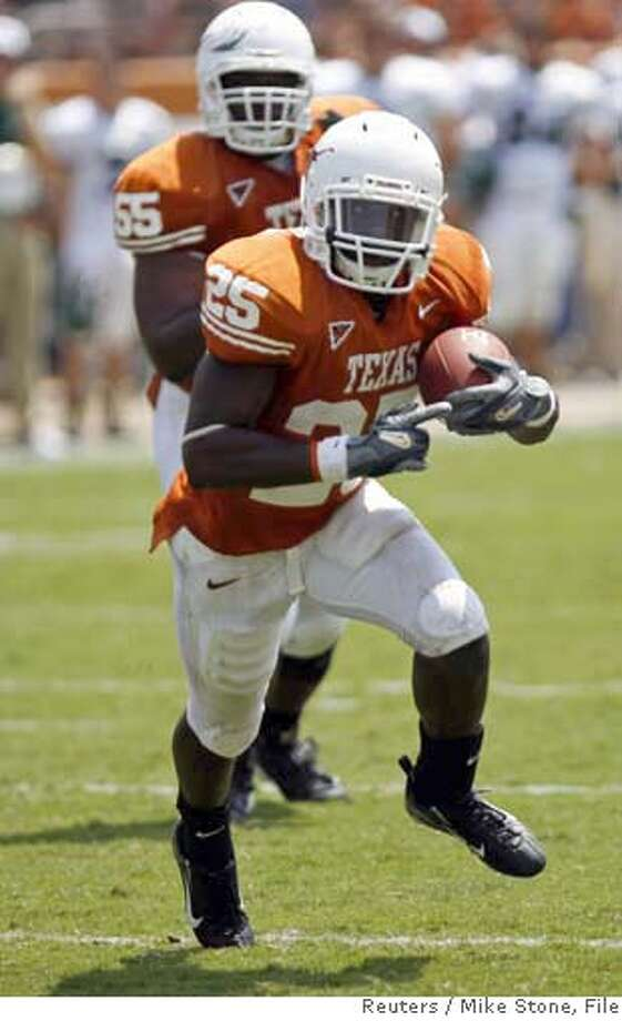 University of Texas running back Jamaal Charles (R) carries the ball as guard Cedric Dockery trails the play during first half action of their NCAA football game against the University of North Texas in Austin, Texas September 2, 2006. REUTERS/Mike Stone (UNITED STATES) Photo: MIKE STONE