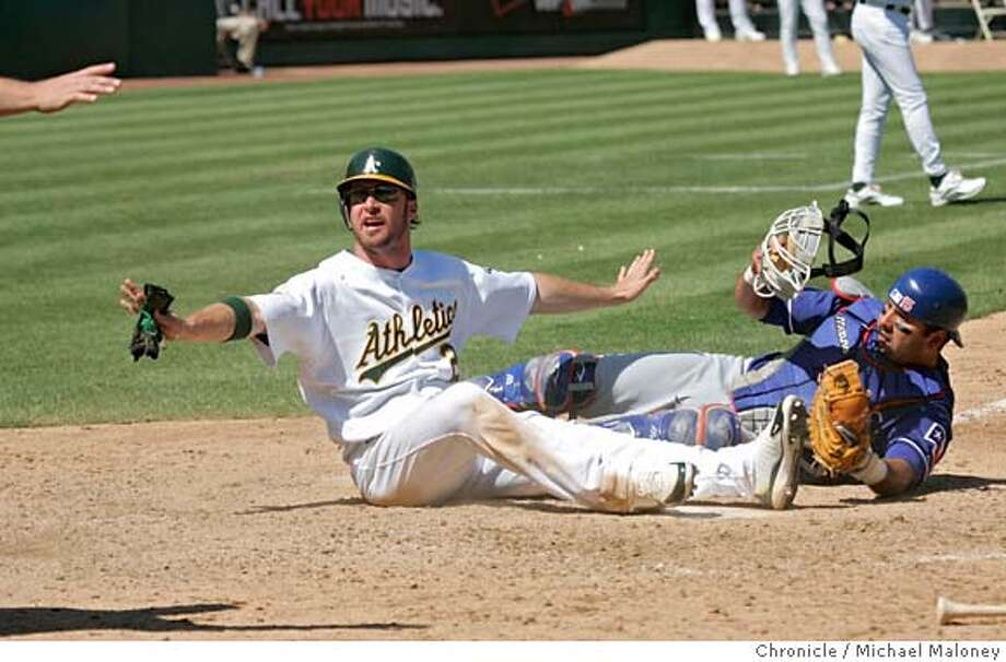 Mark Kotsay signals himself safe at home in the 6th inning on a hit by Milton Bradley. Rangers catcher Gerald Laird never had the ball which is behind him.  Oakland Athletics vs Texas Rangers at McAfee Coliseum. A's won 9-6.  Photo by Michael Maloney / San Francisco Chronicle on 9/6/06 in Oakland,CA Photo: Michael Maloney