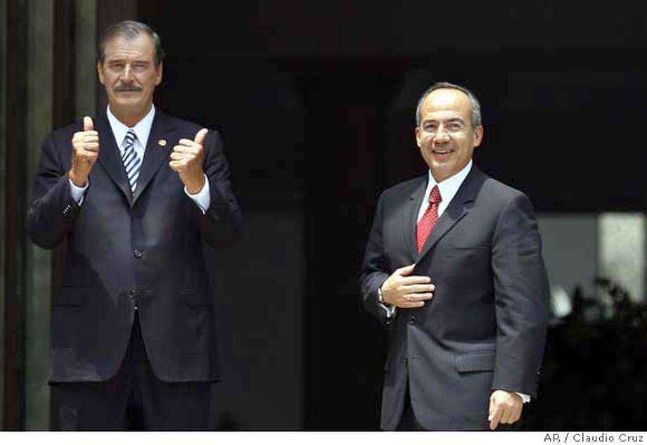 Newly named President-elect Felipe Calderon, right, poses for the cameras with outoing president Vicente Fox at the presidential residence Los Pinos, in Mexico City on Wednesday Sept. 6, 2006. Calderon began working on his new government Wednesday, discussing the transition with outgoing Vicente Fox as his leftist rival fought for the spotlight amid signs his nationwide protest movement is weakening. (AP Photo/ Claudio Cruz) ** EFE OUT ** Photo: CLAUDIO CRUZ