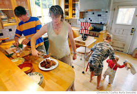 CHEF06_PIRIE_075_CAG.JPG  Foreign Cinema chef Gayle Pirie at her home with partner, John Clark, their daughter, Pearl, 12 mos., and son, Magnus, 7, making her oven baked chicken recipe. This is for the Chef's Night In column.  Photo by Carlos Avila Gonzalez/The San Francisco Chronicle  Photo taken on 8/7/06, in Berkeley, Ca, USA  **All names cq (source) MANDATORY CREDIT FOR PHOTOG AND SAN FRANCISCO CHRONICLE/ -MAGS OUT