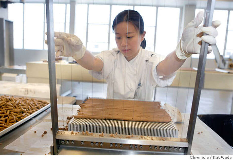 "CHOCOLATE09_015_KW_.jpg Rheena Sy uses a guitar cutter (named by the guitar strings ""blades"") making French Orange Twings, a twist on the traditional truffle using a butter versus creme filling at artisan chocolatier, Chuck Siegel's Charles Chocolates factory in Emeryville Tuesday August 1, 2006. Kat Wade/The Chronicle **Rheena Sy and Chuck Siegel(Subjects) cq Mandatory Credit for San Francisco Chronicle and photographer, Kat Wade, Mags out Photo: Kat Wade"