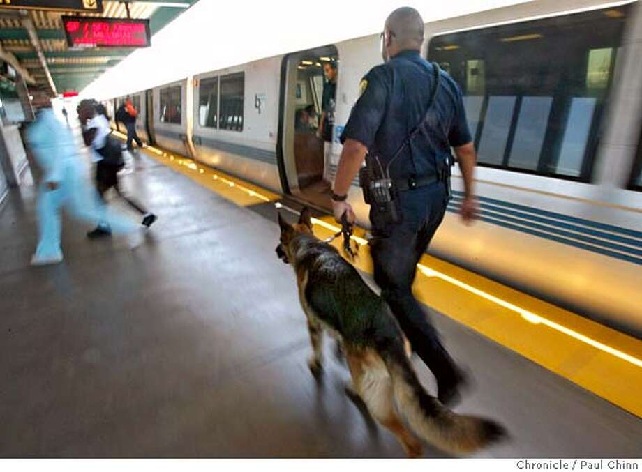 "BART police officer Michael Zendejas and his K-9 partner ""Tim"" inspect an SFO-bound train at the West Oakland BART station in Oakland, Calif. on Thursday, August 10, 2006 following the thwarted terrorist plot in Great Britain.  PAUL CHINN/The Chronicle  **Michael Zendejas MANDATORY CREDIT FOR PHOTOGRAPHER AND S.F. CHRONICLE/ - MAGS OUT Photo: PAUL CHINN"