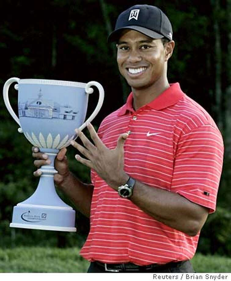 U.S. golfer Tiger Woods holds the tournament trophy after winning the 2006 Deutsche Bank Championship golf tournament in Norton, Massachusetts September 4, 2006. Woods holds up five fingers to show his fifth tournament win in a row. REUTERS/Brian Snyder (UNITED STATES) Photo: BRIAN SNYDER