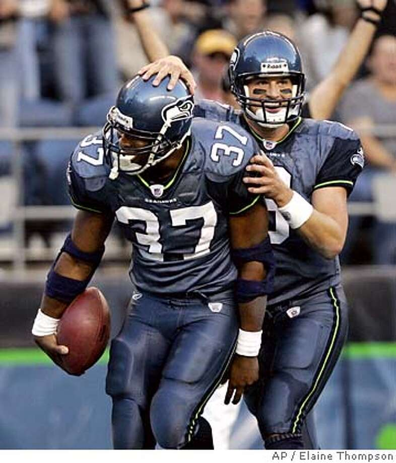 Seattle Seahawks quarterback Matt Hasselbeck, right, gives running back Shaun Alexander (37) a pat after Alexander's first-quarter touchdown run against the Oakland Raiders in the first quarter of an NFL exhibition football game in Seattle, Thursday, Aug. 31, 2006. (AP Photo/Elaine Thompson) Photo: ELAINE THOMPSON