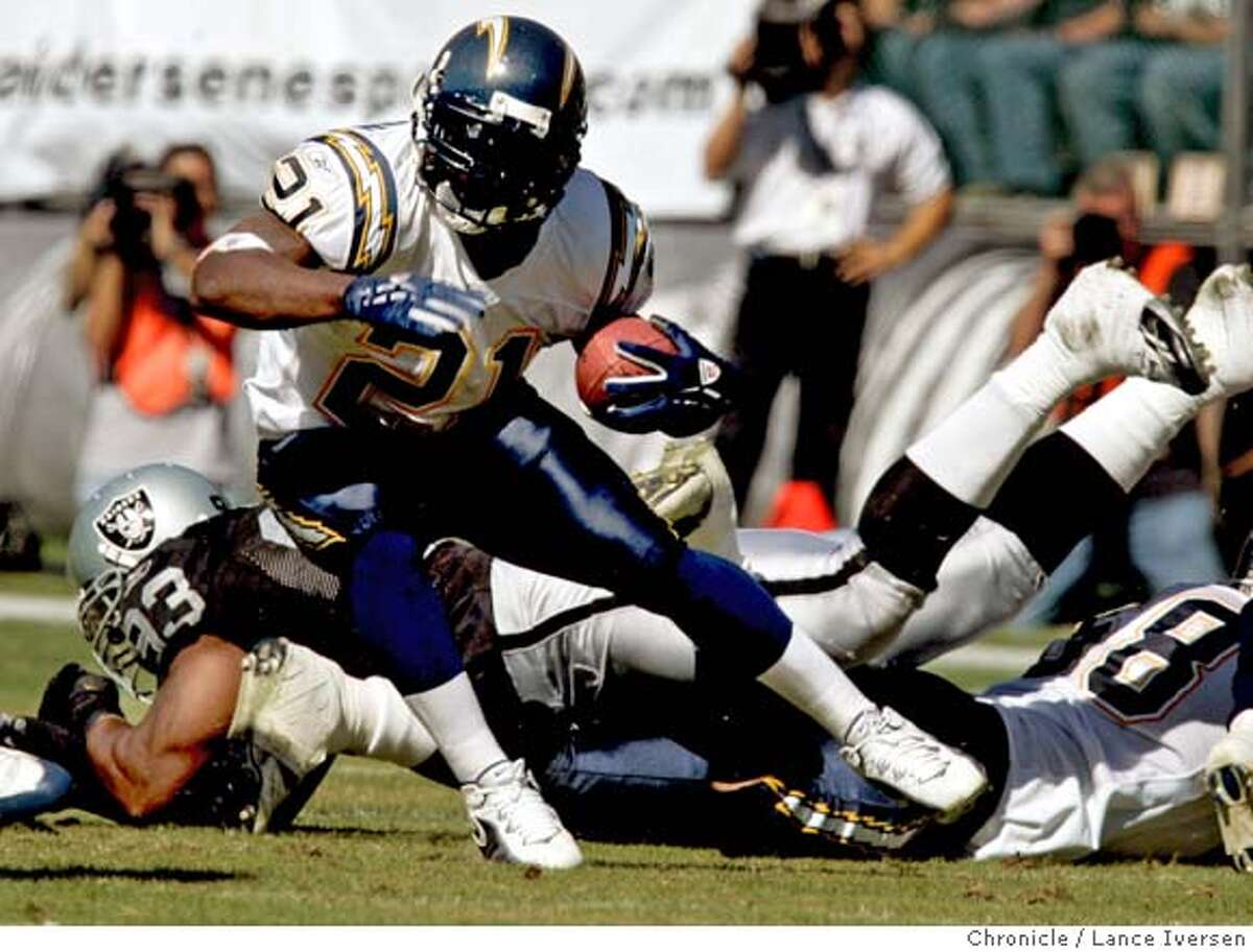 RAIDERS_0155.jpg_ San Diego Chargers #21 LaDainian Tomilinson scrambles for a first down in their 27-14 win over Oakland Raiders at McAfee Coliseum. By Lance Iversen/San Francisco Chronicle Ran on: 10-17-2005 The Raiders must have known LaDainian Tomlinson was coming, but they seemed anything but prepared for the Chargers standout. Ran on: 10-17-2005 The Raiders must have known LaDainian Tomlinson was coming, but they seemed anything but prepared for the Chargers standout. MANDATORY CREDIT PHOTOG AND SAN FRANCISCO CHRONICLE.