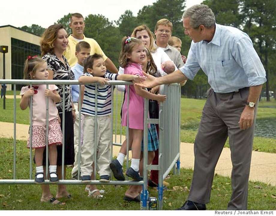 U.S. President George W. Bush (R) greets young onlookers as he arrives for a Labor Day observance at a maritime training institute in Piney Point, Maryland, September 4, 2006. REUTERS/Jonathan Ernst (UNITED STATES) 0 Photo: JONATHAN ERNST
