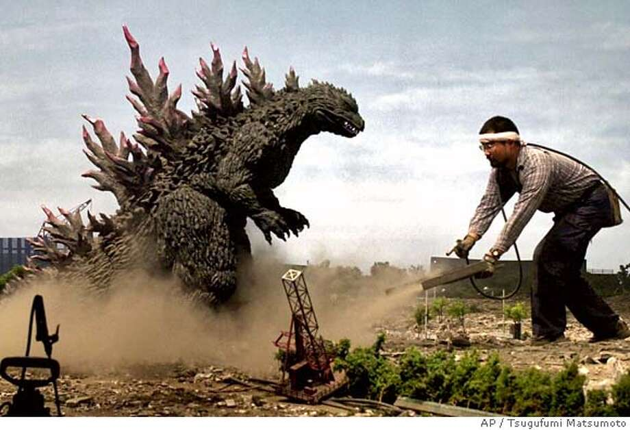 "Godzilla stomps the ground and spread around clouds of dust, being assisted by a Toho Company film production during the filming of Toho's 24th Godzilla movie at its studio in Tokyo Thursday, Aug. 3, 2000. A total of 1,500 legendary lizard fans have applied to a week-long ""see the Godzilla filming tour"" organized by the film production and a travel agency. Showing to the public of the filming of Japan's quintessential B-movie monster is the first time in the 46 years history. The latest movie ""Godzilla versus Megaguirus"" will be shown in Japan early 2001. (AP PHoto/Tsugufumi Matsumoto) DIGITAL IMAGE Photo: TSUGUFUMI MATSUMOTO"