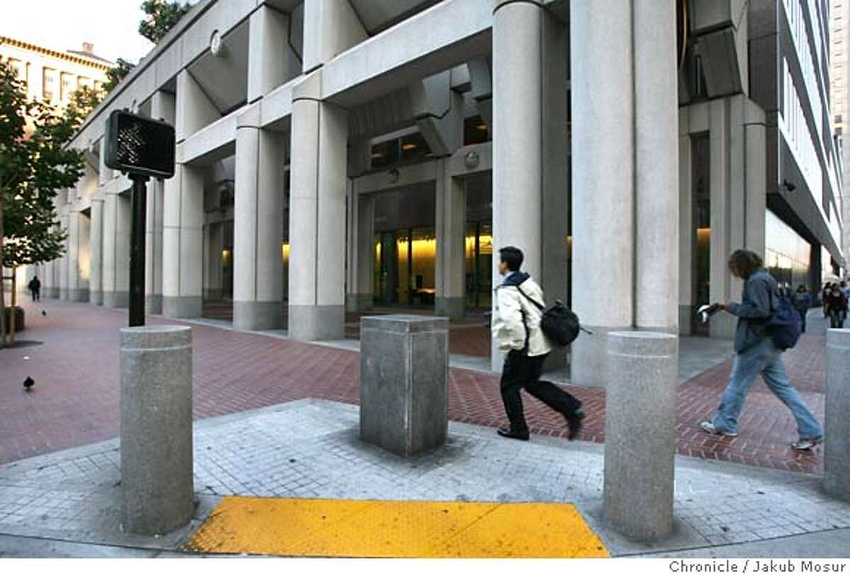 Towers03_12_JMM.JPG A pedestrians walk past barriers in front of the Federal Reserve Bank building. Event on 9/1/06 in San Francisco. JAKUB MOSUR / The Chronicle MANDATORY CREDIT FOR PHOTOG AND SF CHRONICLE/ -MAGS OUT