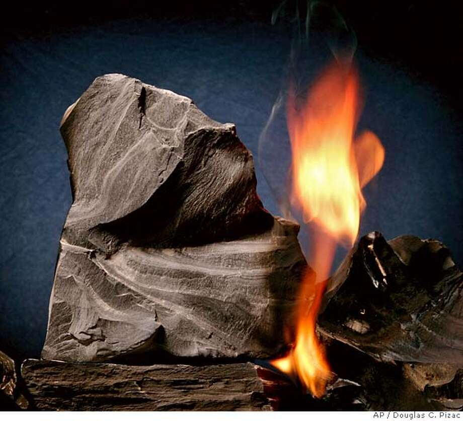 Oil shale rock burns on its own once lit with a blow torch Monday, Aug. 15, 2005, in Sandy, Utah. Oil shale is rock containing deposits of oil. Companies have spent years researching how to melt oil from the rock. (AP Photo/Douglas C. Pizac) Photo: DOUGLAS C. PIZAC