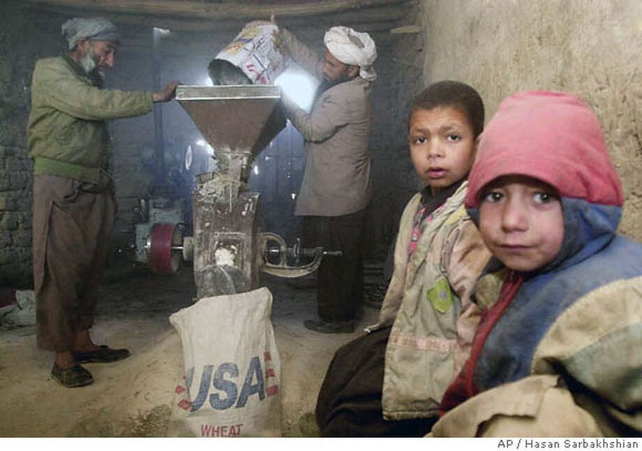 Afghans grind wheat from the United States in a refugee camp near Heart. U.S. aid often comes in the form of U.S. profits. Associated Press file photo, 2001, by Hasan Sarbakhshian