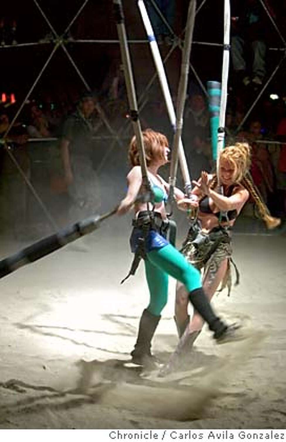 Two Burning Man participants do battle in the Thunderdome on Saturday, September 2, 2006. The look and feel of the Burning Man Festival changes dramatically as day gives way to night. When the sun falls, the art and flare of the Playa become louder, brighter, and more intense as even the participants' behavior changes to match. Daily coverage of the Burning Man festival in the Nevada desert. Photo by Carlos Avila Gonzalez/The San Francisco Chronicle Photo taken on 9/3/06, in Black Rock City, Nv, USA **All names cq (source)