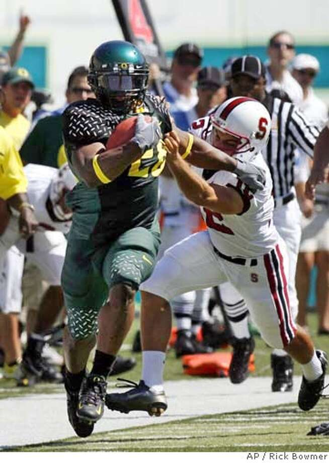 ** CORRECTS ID TO JONATHAN STEWART , NOT J.D. NELSON ** Oregon's Jonathan Stewart , left, breaks free from Stanford's Derek Belch in the first quarter of their college football game Saturday, Sept. 2, 2006, in Eugene, Ore. Oregon defeated Stanford, 48-10. (AP Photo/Rick Bowmer) Photo: RICK BOWMER