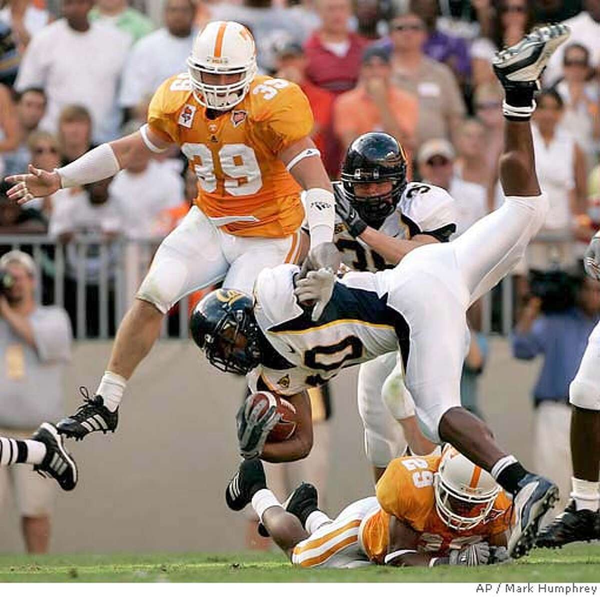 California tailback Marshawn Lynch (10) is tripped-up by Tennessee's Inquoris Johnson (29) in the first quarter of their college football game on Saturday, Sept. 2, 2006, in Knoxville, Tenn. Also defending for Tennessee is Ryan Karl (39). (AP Photo/Mark Humphrey)