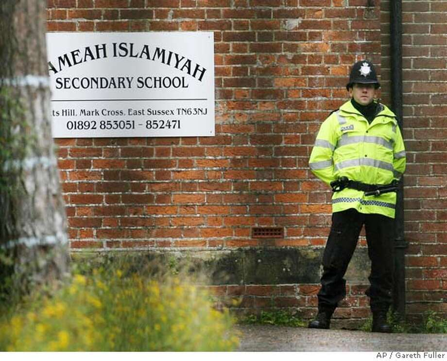 A British police officer stands guard outside Jameah Islamiyah Secondary School in Mark Cross, East Sussex, England, Saturday, Sept. 2, 2006. Police arrested 14 people in raids around London and said Saturday they suspected the men had been involved in training and recruiting for terror attacks. A Muslim school in East Sussex, south of London, also was being searched Saturday, news reports said. (AP Photo/Gareth Fuller,PA) ** UNITED KINGDOM OUT NO ARCHIVE ** UNITED KINGDOM OUT NO ARCHIVE - PHOTOGRAPH CAN NOT BE STORED OR USED FOR MORE THAN 14 DAYS AFTER THE DAY OF TRANSMISSION Photo: GARETH FULLER