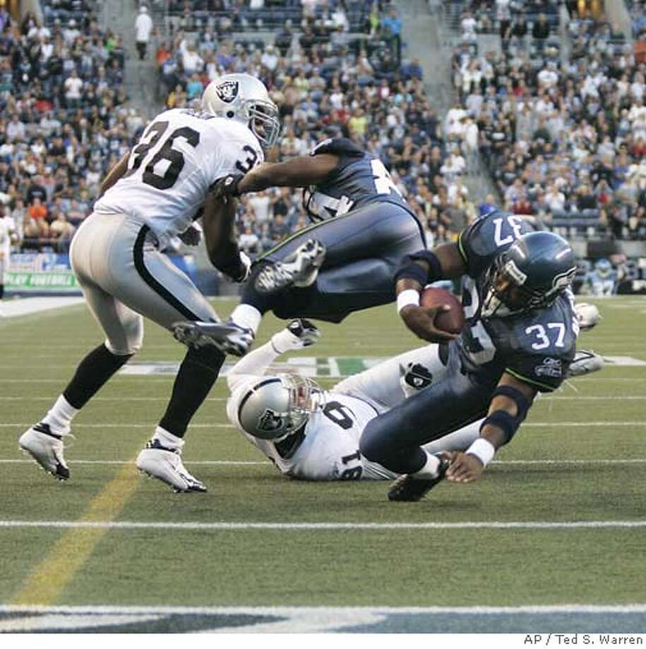 Seattle Seahawks running back Shaun Alexander (37) dives for a touchdown as Seahawks wide receiver Bobby Engram, second from left, flies through the air after making a well-placed block on Oakland Raiders safety Derrick Gibson, left, and a missed tackle by Raiders defensive end Tyler Brayton (91) in the first quarter of an NFL exhibition football game Thursday, Aug. 31, 2006, at Qwest Field in Seattle. (AP Photo/Ted S. Warren) Photo: TED S. WARREN