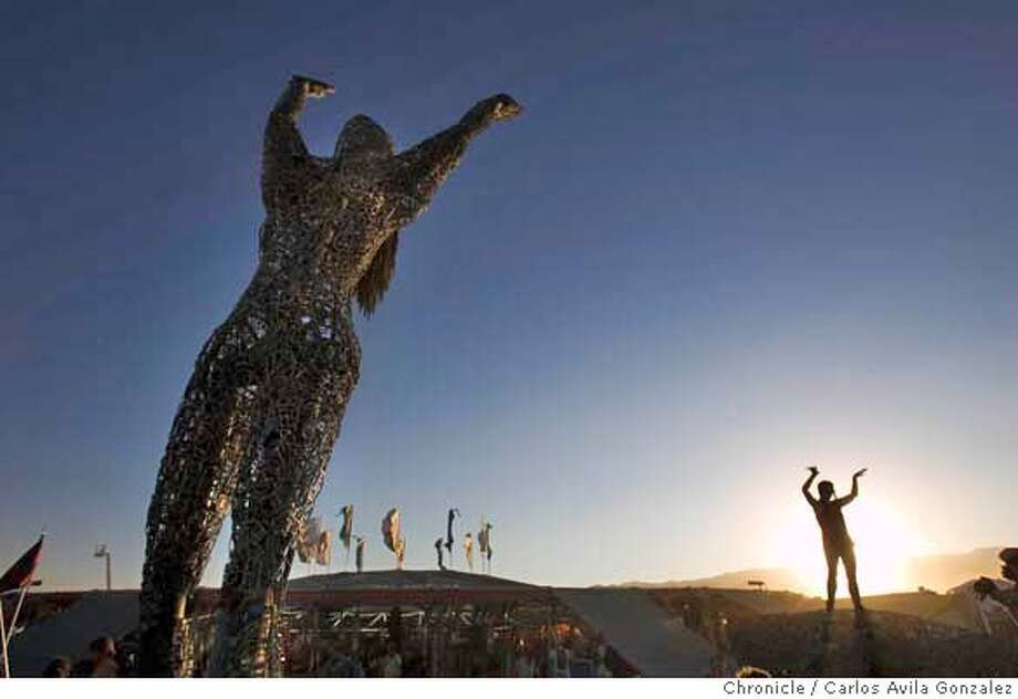 BURNINGMAN_014_CAG.JPG  A Burning Man participant dances near a sculpture at Center Camp during the Burning Man Festival on Tuesday, August 29, 2006. Daily coverage of the Burning Man festival in the Nevada desert. Photo by Carlos Avila Gonzalez/The San Francisco Chronicle  Photo taken on 8/29/06, in Black Rock City, Nv, USA  **All names cq (source)  Ran on: 09-01-2006  A visitor dances, above, near a sculpture at Center Camp during the Burning Man Festival on Tuesday. Monkey Boy (his playa name), right, is ready for action in spiral goggles and dust mask. The counterculture festival is held annually in the Black Rock Desert just north of Gerlach in northern Nevada. About 38,000 attendees are expected. The festival runs through Labor Day.  Ran on: 09-01-2006 Photo: Carlos Avila Gonzalez