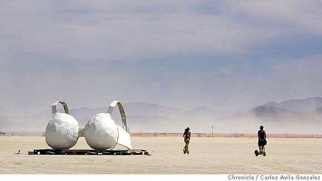 Two Burning Man participants ride by an art installation resembling a bra in the desert on Tuesday, August 29, 2006. Daily coverage of the Burning Man festival in the Nevada desert. Photo by Carlos Avila Gonzalez/The San Francisco Chronicle  Photo taken on 8/29/06, in Black Rock City, Nv, USA  **All names cq (source) Photo: Carlos Avila Gonzalez