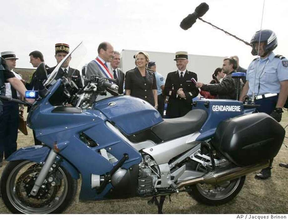 French Defense Minister Michelle Alliot-Marie, center, is being presented the new Yamaha FJR 1300 equiped for French gendarmes, Tuesday June 21, 2005 in Paris. Some 370 new motorcycles have been ordered by the defense ministry. (AP Photo/Jacques Brinon) Photo: JACQUES BRINON