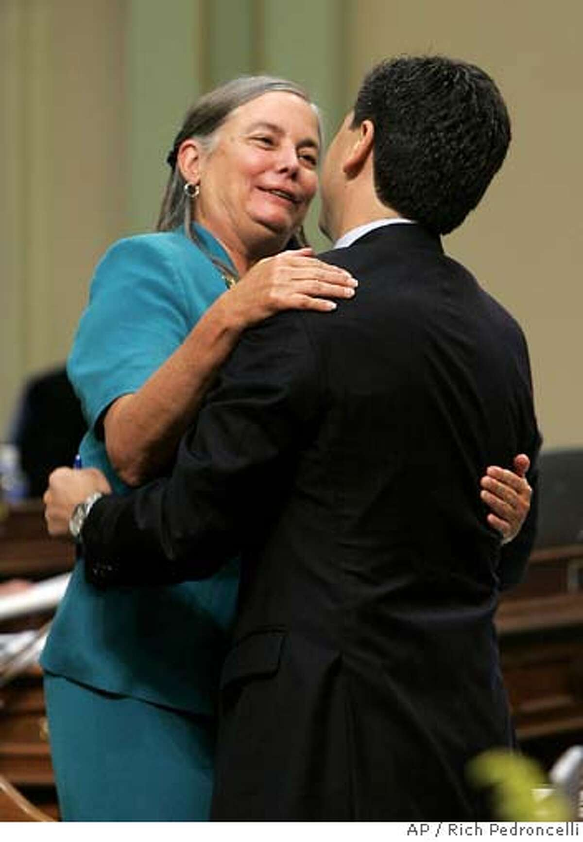 Assembly Speaker Fabian Nunez, D-Los Angeles, right, hugs Assemblywoman Fran Pavley, D-Agoura Hills, after her global warming bill was approved by the Assembly at the Capitol in Sacramento, Calif., Thursday, Aug. 31, 2006. The measure, approved by a 47-31, will make California the first state to impose a cap on all greenhouse gas emissions, including those from industrial plants.(AP Photo/Rich Pedroncelli)