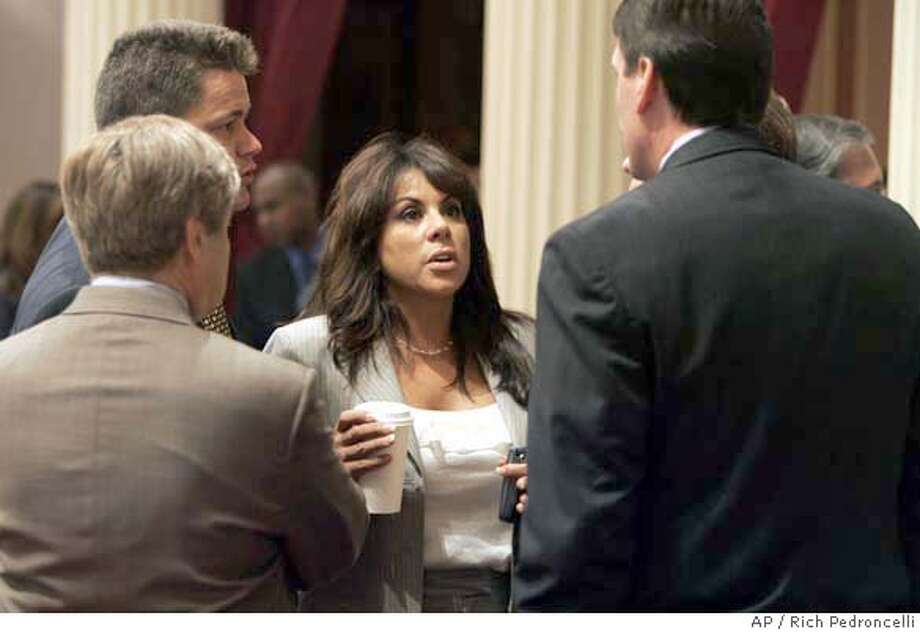 Assemblywoman Bonnie Garcia, of Cathedral City, center, talks with fellow Republican lawmakers state Sen. George Runner, of Lancaster, left, Assemblyman Russ Bogh, of Yucaipa, background left, and Assembly Republican Leader George Plescia, of San Diego, right, on the floor of the state Senate at the Capitol in Sacramento, Calif., Thursday, Aug. 31, 2006. Garcia was trying to get support for her measure that would approve a gaming compact worked out between Gov. Arnold Schwarzenegger and the Agua Caliente Band of Cahuilla Indians.(AP Photo/Rich Pedroncelli) Photo: RICH PEDRONCELLI