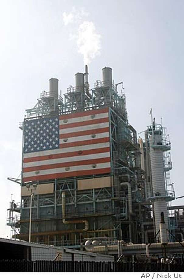 A U.S. flag hangs on a structure at an oil refinery in Carson, Calif., Thursday, Aug. 31, 2006. California will become the first state to impose a cap on all greenhouse gas emissions under a landmark deal reached Wednesday, by Gov. Arnold Schwarzenegger and legislative Democrats. (AP Photo/Nick Ut) Photo: NICK UT