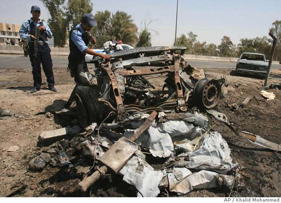 Iraqi policemen inspect the wreckage of a car used by suicide car bomber, in Baghdad,Iraq, Thursday Aug. 31, 2006. A suicide car bomber targeting a Baghdad gas station killed two people and wounded 13 on Thursday, a day after dozens died across the country as the U.S. president insisted American troops must stay in Iraq until the job is done. (AP Photo/Khalid Mohammed) Photo: KHALID MOHAMMED