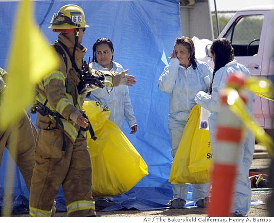 Three women are escorted by Kern County Fire Department personal to a medical triage area after being decontaminated for exposure to a sulfur-based pesticide while working in an agriculture field Thursday, Aug. 31, 2006, near Arvin Calif. Twenty grape farm workers became sick Thursday when fungicide from a neighboring vineyard drifted over them south of Bakersfield, county agriculture officials said. (AP Photo/The Californian, Henry A. Barrios) ** MANDATORY CREDIT MAGS OUT TV OUT ONLINES OUT ** Photo: HENRY A. BARRIOS