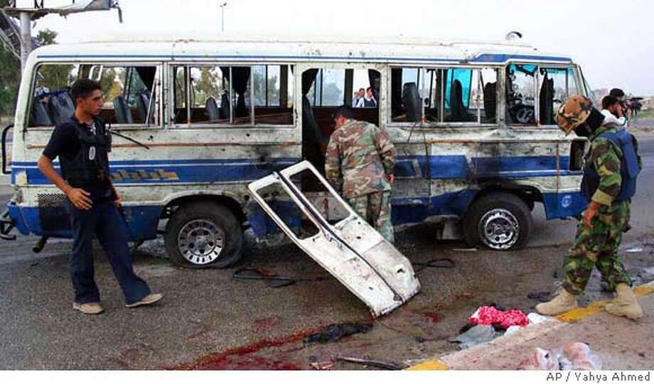Iraqi army soldiers inspect the damaged minibus, in Kirkuk, 290 kilometers (180 miles) north of Baghdad, Iraq, Wednesday Aug. 30, 2006, after a suicide bomber blew himself up inside the bus, killing three people wounding 11 others in the predominantly Christian neighborhood of Arafa, police said. (AP Photo/Yahya Ahmed) Photo: YAHYA AHMED