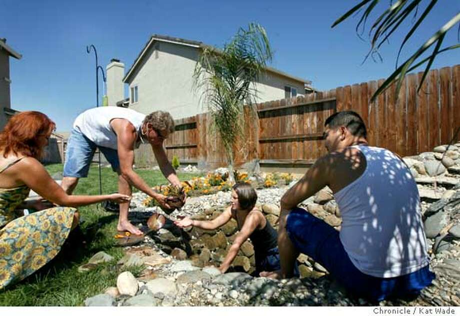 PLUMAS_LAKE_229_KW_.jpg  (L to R) Robin Moss,( neighbor and engineer Dave Johns (916)595-5904), Giuffria Bartholomew (Mosses daughter) and Sam Kim plant a lily after installing a pump in the Koi Carp pond and waterfall Kim had built in the backyard of his home in the new Plumas Ranch developement bordered by Highway 70 on the East and Feather River Blvd. on the south in Plumas Lake on Sunday August 20, 2006 is built in a flood plain that went underwater in the floods of 1997, killing 3 people.  Kat Wade/The Chronicle ** Robin Moss, Dave Johns, Giuffria Bartholomew and Sam Kim (Subjects) cq  Ran on: 08-31-2006  Robin Moss, above in center with family and friends, plants a lily after installing a pump in the koi (carp) pond in the backyard of his home in the new Plumas Lake project. The development, at left, is in a flood plain and is shown to be lower than Feather River Boulevard.  Ran on: 08-31-2006  Robin Moss, above in center with family and friends, plants a lily after installing a pump in the koi (carp) pond in the backyard of his home in the new Plumas Lake project. The development, at left, is in a flood plain and is shown to be lower than Feather River Boulevard. Photo: Kat Wade
