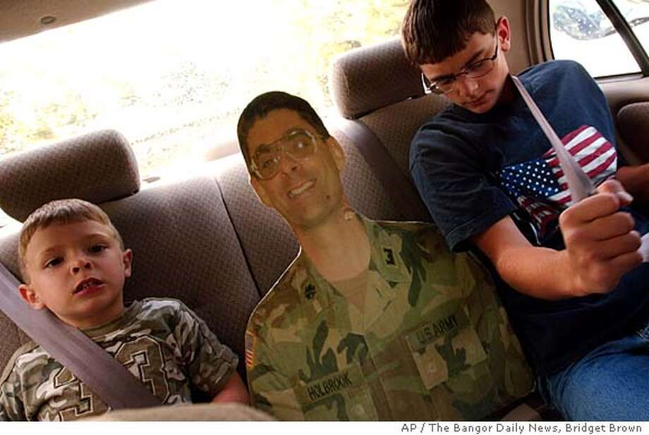 "Logan Holbrook, 3, left, and his brother, Justin, 14, both of Hermon, Maine, squeeze in on either side of their ""flat daddy,"" a foam-board cut-out of their father, Lt. Col. Randall Holbrook, on their way to dinner last week in Hampden, Maine. The family has had their ""flat daddy"" since Jan. 28, 2006, three days after Holbrook was deployed to Afghanistan with his Army National Guard engineering unit. (AP Photo/The Bangor Daily News, Bridget Brown) ** MANDATORY CREDIT, MAGS OUT, , INTERNET OUT ** Photo: BRIDGET BROWN"